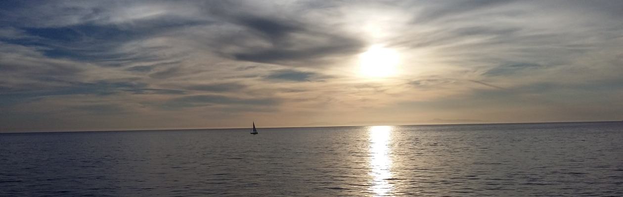 Sunset over ocean with sailboat in distance